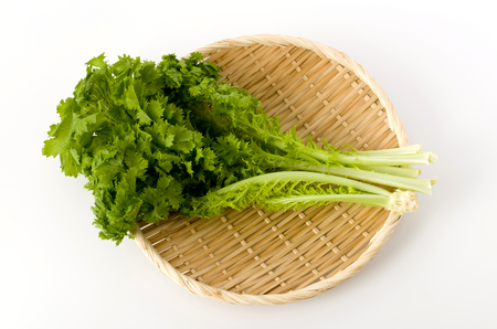 wasabi greens on a bamboo colander on white background 免版税图像
