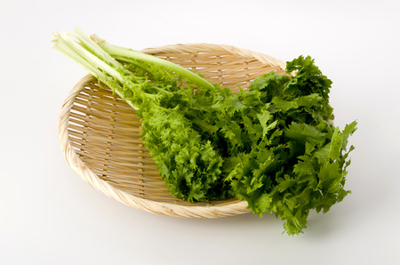 wasabi greens on a bamboo colander on white background Archivio Fotografico