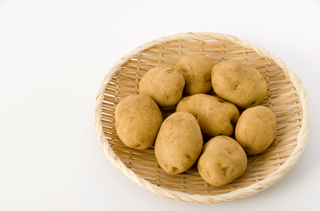 Potato isolated on bamboo colander on white background