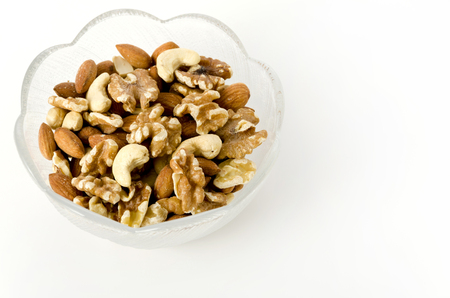 mix of nuts in a glass bowl on a white background