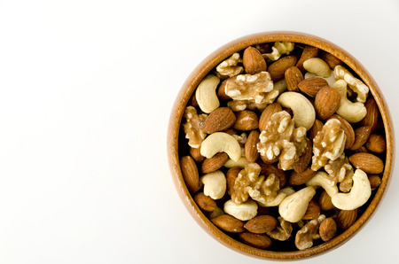 mix of nuts in a wooden bowl on a white background