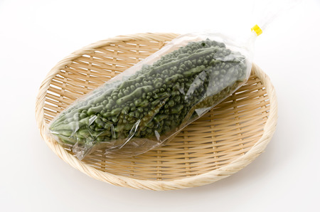 Bitter melon in Plastic bag on bamboo colander on white background Stock Photo