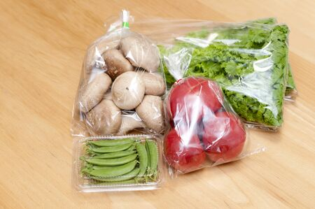 Fresh Shiitake Mushroom, Tomatoes, snap pea, Wasabi green Vegetables in Plastic bag on wooden background. Shopping in the store.