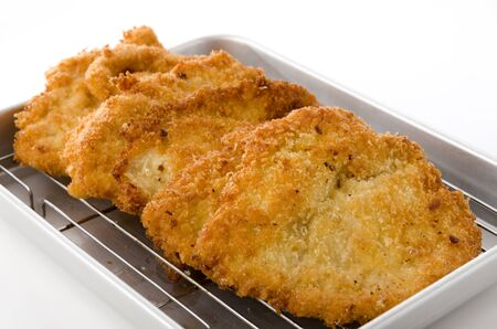 Breaded Chicken strips on Aluminum tray on white background. Chicken tender cutlet.