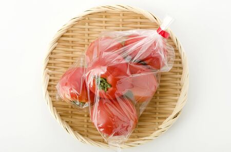Ripe red Tomatoes in Plastic bag on bamboo colander 스톡 콘텐츠