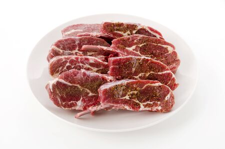 Raw lamb chops on White Plate on White background