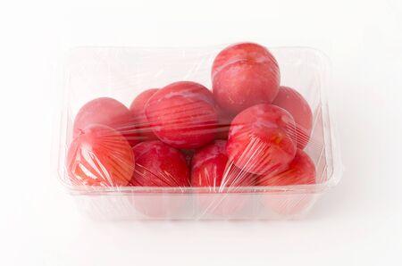 Barquette de prune japonaise fraîche (Prunus salicina) sur fond blanc Banque d'images