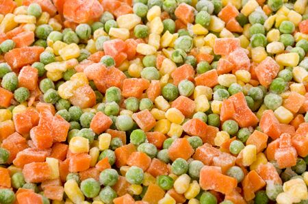 Frozen diced vegetables background with carrot, corn and peas. Stock fotó