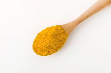 Turmeric (Curcuma) powder in wooden spoon on white background