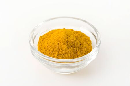 Turmeric powder in Glass Bowl on white background