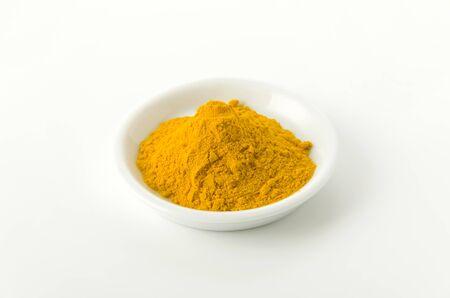 Turmeric (Curcuma) powder on dish on white background Stock Photo