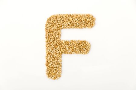toasted sesame seeds letter F uppercase of English alphabet isolated on white background