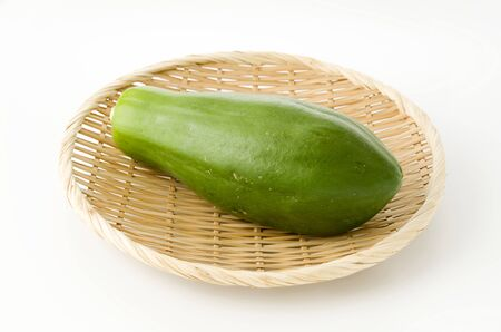 Green Papaya on bamboo colander on white background