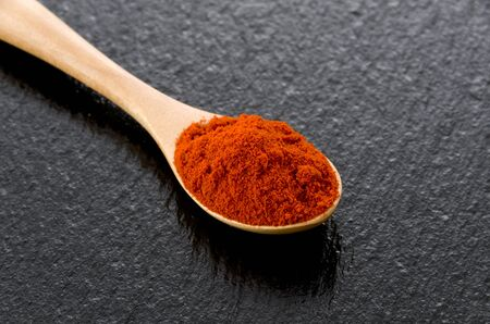Paprika powder in wooden spoon on black stone background