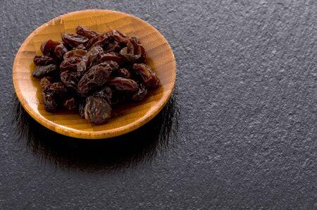 Raisins in small wooden dish on black stone background 스톡 콘텐츠
