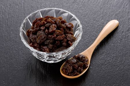 Raisins in Glass bowl on black stone background