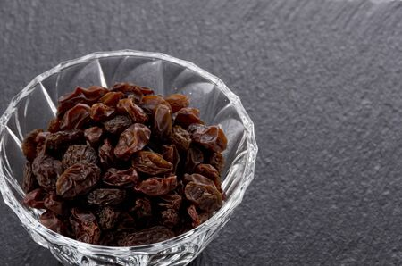 Raisins in Glass bowl on black stone background