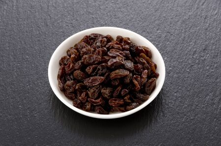 Raisins in small dish on black stone background