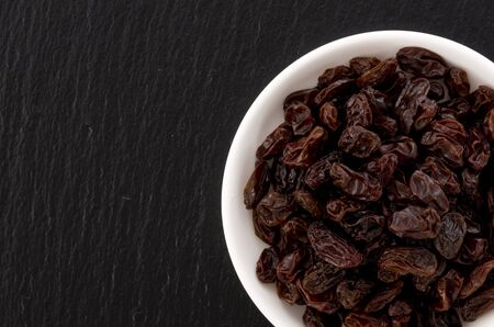 Raisins in small dish on black stone background