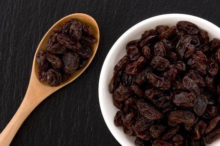 Raisins in saucer on black stone background