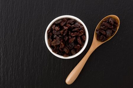 Raisins in saucer on black stone background Imagens