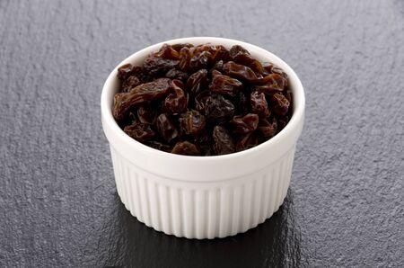 Raisins of white cocotte on black stone background