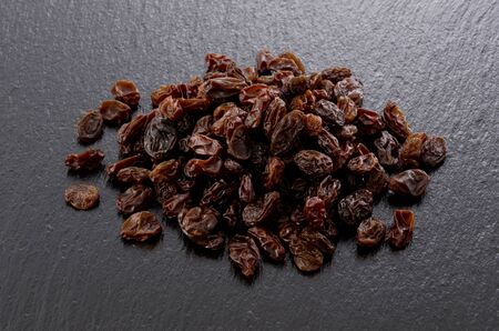 Raisins on black stone background 스톡 콘텐츠