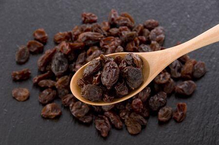 Raisins in wooden spoon on black stone background Foto de archivo