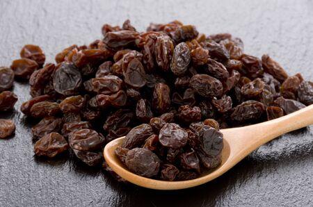 Raisins in wooden spoon on black stone background 스톡 콘텐츠