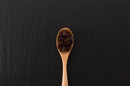 Raisins in a wooden spoon on black stone background