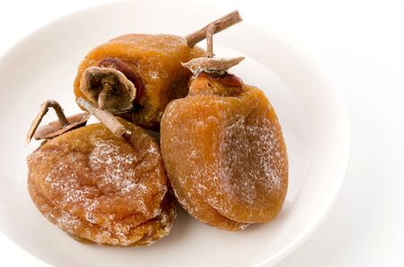 Dried persimmon on a plate white background