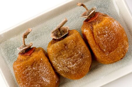 Dried persimmon on a plate on white background