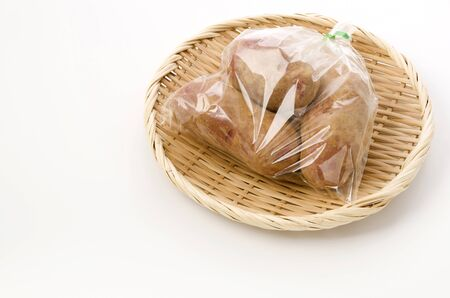 fresh red skinned potatoes with soil in plastic bag on bamboo colander on white background