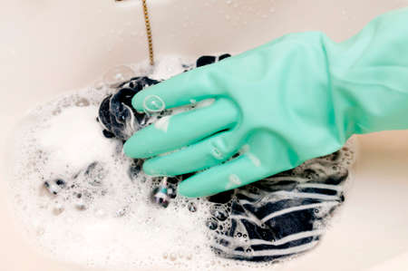 hand in a rubber glove washes clothing