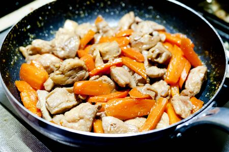 Cooking chicken meat with carrot in a pan. Imagens