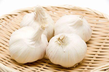 Fresh garlic in bamboo colander on white background