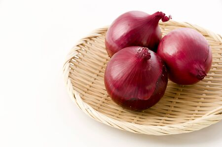 Fresh red onion in bamboo colander on white background
