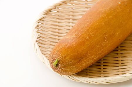 Okinawan Yellow cucumber in Bamboo colander on white background