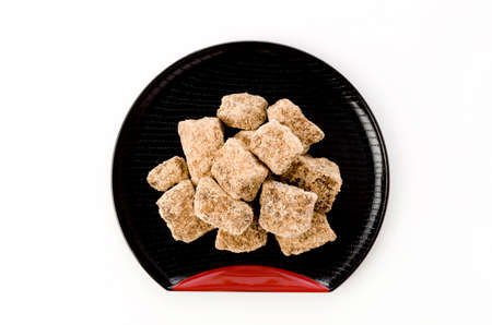 brown sugar lump in black plate on white background