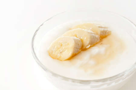 Yogurt with banana slices on a white background Standard-Bild