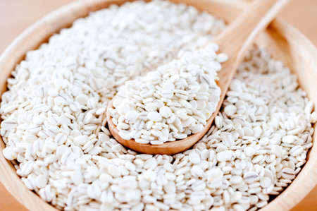 rolled barley in a wooden bowl on white background Standard-Bild