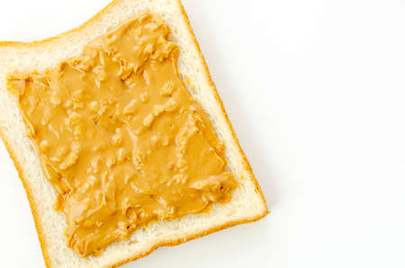 peanut butter on a slice of white bread.