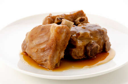 Stewed pork ribs on white plate on white background
