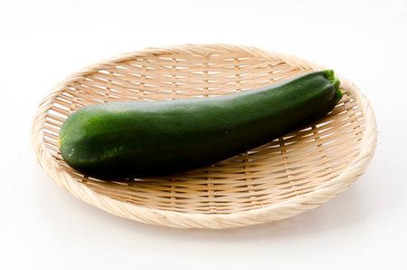 fresh raw zucchini on a bamboo sieve on white background 版權商用圖片