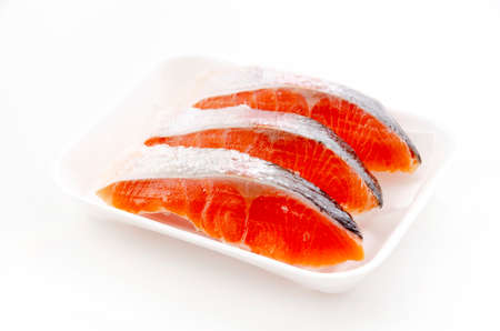 Raw fillet trout salmon in foam tray on white background