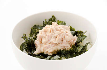 Japanese food, Tuna Mayo Don, Tuna mayonnaise with rice and nori in a white pottery bowl on a white background.
