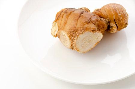 fresh ginger on white plate on white background
