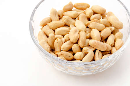 Roasted salted peanuts in a transparent glass bowl on a white background 版權商用圖片