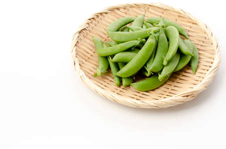 sugar snap pea on bamboo sieve on white background
