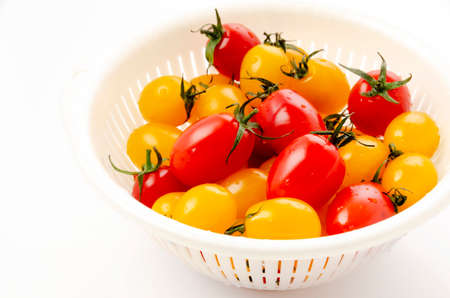 Fresh cherry tomatoes aiko in a plastic colander on white background